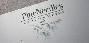 Logo for Pine Needles Quilting Shop - Bend, Oregon